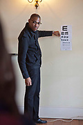 A male optician points at letters on the Snellen chart stuck to a wall in a classroom in Zonnebloem School, Cape Town, South Africa.  The optician works for Mullers, who volunteer their staff to visit schools and perform eye tests on all children in school grade 2.
