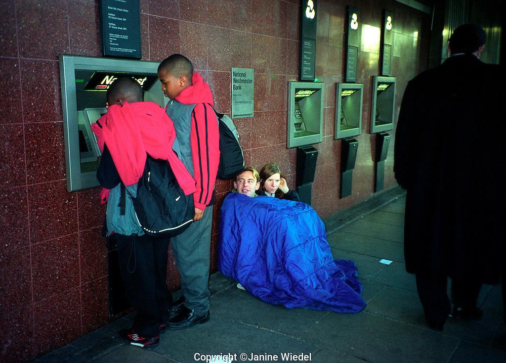 Homeless couple begging on Victoria Street under cash point dispenser.