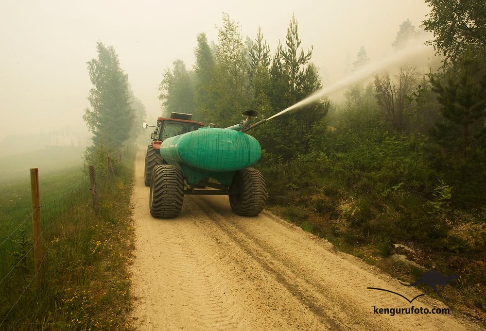 Froland 20080612:<br /> Røyken ligger tett over tettstedet Belland der det ble utført evakuering torsdag ettermiddag. Her prøver en lokal bonde å fukte skogen med vann fra en tank på traktoren.<br /> Foto: Tor Erik Schrøder / SCANPIX