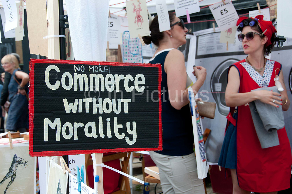 Buxton Street off Brick Lane, East London. June 8th 2014. Vauxhall Art Car Boot Fair.Tinsel and Twinkle's Revolution launderette. Sign saying 'No more commerce without morality'.