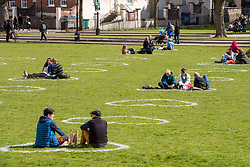 © Licensed to London News Pictures;11/04/2021; Bristol, UK. People enjoy the spring weather and sunshine sitting inside socially distanced heart shapes on College Green and other open spaces in the city which have been painted with Love Bristol stencils during the Covid-19 coronavirus pandemic in England as lockdown restrictions are due to be eased further on Monday 12 April. This is the #LoveBristol campaign to welcome visitors back to the city safely and support local businesses as they reopen from Monday. Photo credit: Simon Chapman/LNP.