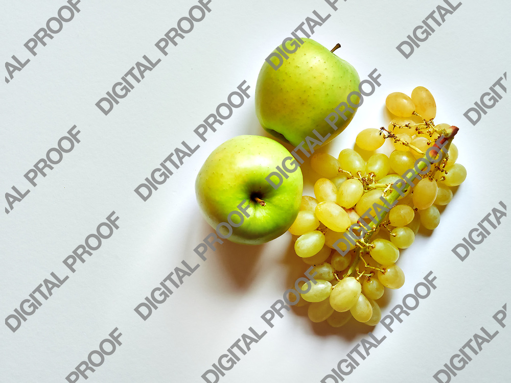 Above view of isolated set of a green apple with a bunch of sweet seedless grapes in studio with white background