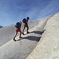 Hikers ascend glacier-polished granite slabs on Daff Dome near Tuolumne Meadows in Yosemite National Park, California.