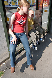 Older sister waiting at a bus stop with her younger brothers,