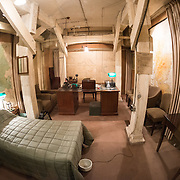 Winston Churchill's bedroom and office at the Churchill War Rooms in London. The museum, one of five branches of the Imerial War Museums, preserves the World War II underground command bunker used by British Prime Minister Winston Churchill. Its cramped quarters were constructed from a converting a storage basement in the Treasury Building in Whitehall, London. Being underground, and under an unusually sturdy building, the Cabinet War Rooms were afforded some protection from the bombs falling above during the Blitz.