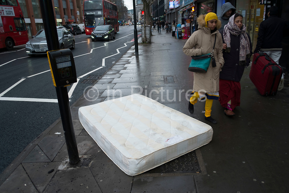 Local Asian women walk past a discarded matress thrown out onto Whitechapel Road in East London, England, United Kingdom. (photo by Mike Kemp/In Pictures via Getty Images)