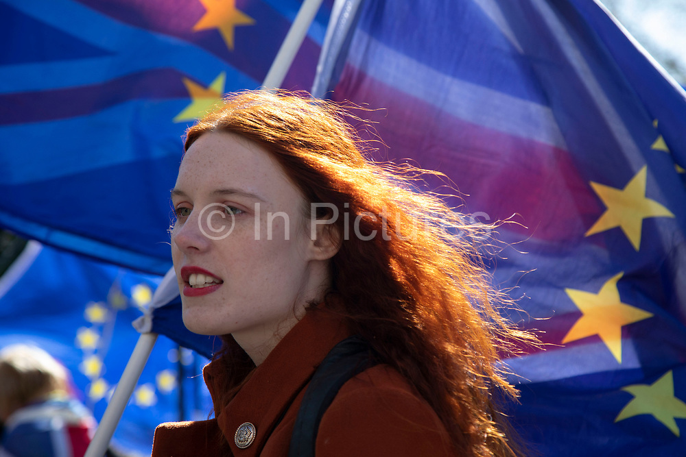 Young anti Brexit protester Florine Pochet from Lille in France shouts anti-Brexit slogans and waves her flags opposite Parliament in Westminster as the Prime Minister arrives in Brussels to request an extension to Article 50 so the UK can continue to try to agree a Brexit Withdrawal Agreement on 10th April 2019 in London, England, United Kingdom. With just two days until the UK is supposed to be leaving the European Union, the delay decision awaits.