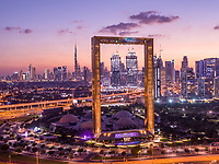 Aerial view of Dubai Frame, an iconic building in Dubai downtown with city skyline in background during a beautiful sunset, United Arab Emirates.