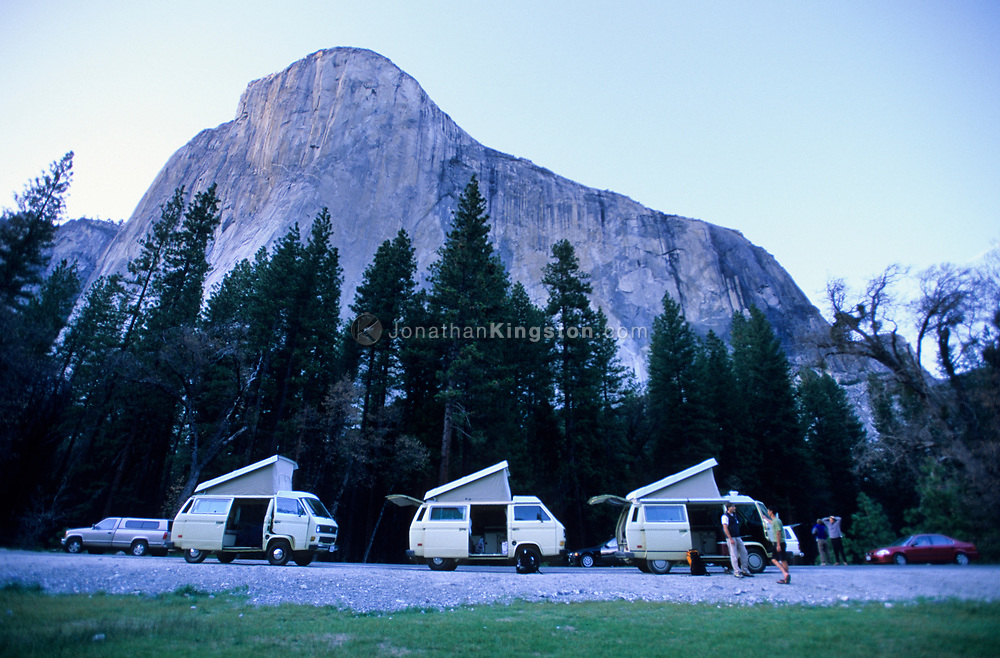 YOSEMITE, CA –  Climbers stand in front of their Volks Wagon Camper vans parked underneath El Capitan in Yosemite National Park, California.  VW Westfalia camper vans are a favorite mode of transportation for rock climbers due to the large storage space for gear and the built in stove and refrigerator. (Model Released)