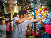 """27 NOVEMBER 2012 - BANGKOK, THAILAND: A man shoots a sling shot at targets in a booth on the midway at the Wat Saket Temple Fair in Bangkok. Wat Saket, popularly known as the Golden Mount or """"Phu Khao Thong,"""" is one of the most popular and oldest Buddhist temples in Bangkok. It dates to the Ayutthaya period (roughly 1350-1767 AD) and was renovated extensively when the Siamese fled Ayutthaya and established their new capitol in Bangkok. The temple holds an annual fair in November, the week of the full moon. It's one of the most popular temple fairs in Bangkok. The fair draws people from across Bangkok and spills out in the streets around the temple.    PHOTO BY JACK KURTZ"""