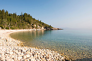 Round stones and clear sea on Orkos Beach on the east coast of Paxos, The Ionian Islands, The Greek Islands Greece, Europe