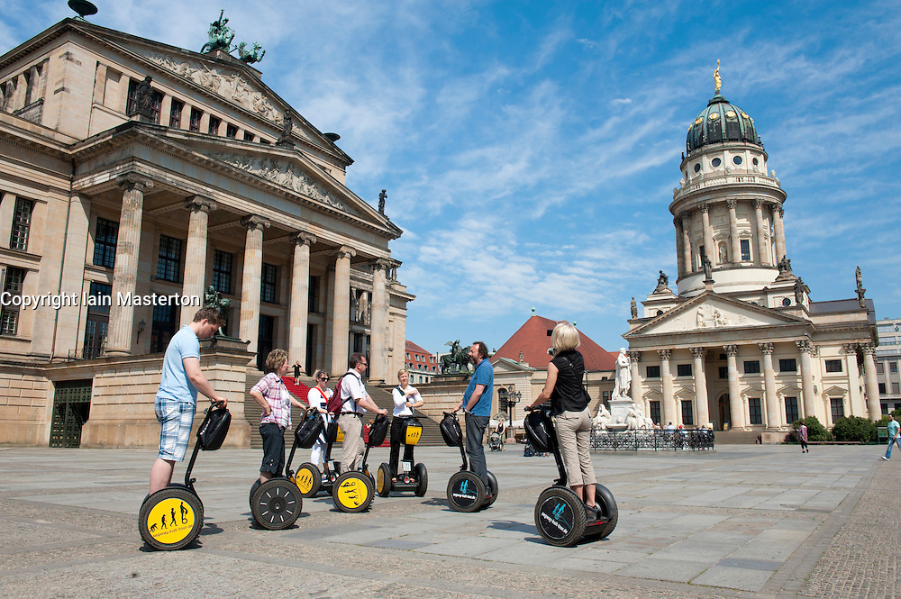 Tourists on segway tour in Gendarmenmarkt square and Konzerthaus and Franzosischer Dom in Mitte district of Berlin Germany