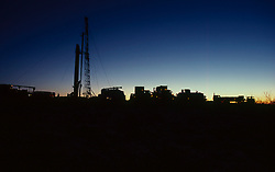 Stock photo of the silhouette of trucks at an on-shore drilling site