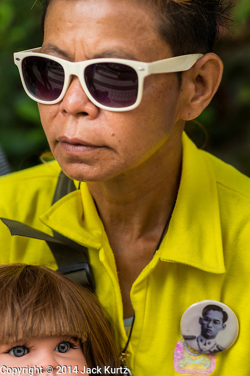 09 OCTOBER 2014 - BANGKOK, THAILAND: A woman wearing a yellow shirt and button with a photo of Bhumibol Adulyadej, the King of Thailand, waits to get into Siriraj Hospital to pray for the King. People wear yellow when they pray for the King because it's the King's color. The King has been hospitalized at Siriraj Hospital since Oct. 4 and underwent emergency gall bladder removal surgery Oct. 5. The King is also known as Rama IX, because he is the ninth monarch of the Chakri Dynasty. He has reigned since June 9, 1946 and is the world's longest-serving current head of state and the longest-reigning monarch in Thai history, serving for more than 68 years. He is revered by the Thai people and anytime he goes into the hospital thousands of people come to the hospital to sign get well cards.   PHOTO BY JACK KURTZ