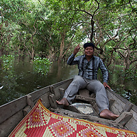 My friend and guide Mab, sitting in a boat in a flooded mangrove forest located near the Kompong Phluk floating village.