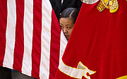 11/18/16- St. Paul, Minn. Nervously watching from her seat, peering between an American flag and a Marine Corps flag,  Nasue Xiong, a St. Paul, MN Como Park Senior High School junior and a member of the ROTC, observed fellow cadets  as they marched in a color guard drill during a competition at Washington Technology Magnet School.