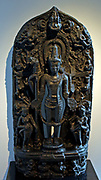Vishnu with attendants.  Pala period, 1000-1100, India, West Bengal, stone.  The four-armed god holds his attributes, the mace, discus and conch, and with his fourth hand he makes the gesture of beneficence (varada).  The various incarnations of Vishnu appear in the small scenes above the two attendants.