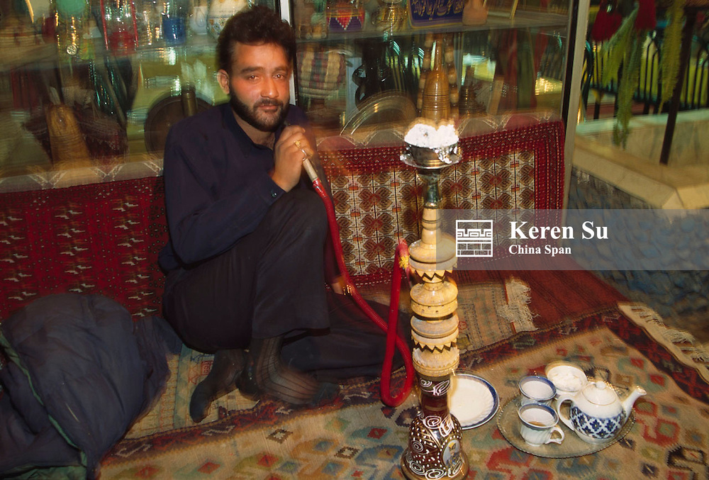 Iranian people dining and smoking traditional water pipe at a restaurant, Iran