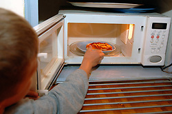 boy heats up his microwave meal