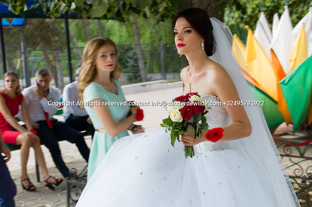 20150829  Moldova, Transnistria,Pridnestrovian Moldavian Republic (PMR) Dubushari. A young girl that just got married walks to her friends holding flowers. Her young friends sit in the backgroud. Marriage is the biggest life event in every girls' life.