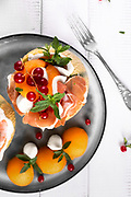 Italian appetizer with melon prosciutto and mozzarella cheese decorated with mint leaves and red currant top view closeup shot