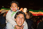 """15 SEPTEMBER 2005 - MEXICO CITY: Revelers, a father and son, on the Zocalo in Mexico City, Sept 15, for the traditional """"grito,"""" the shout of """"Viva Mexico"""" that marks the official start of Mexican Independence Day celebrations. Although Mexican Independence Day is Sept. 16, the celebrations usually start a couple of days before and continue through the 17th or 18th or September. It is the most important holiday on the Mexican calender. PHOTO BY JACK KURTZ"""