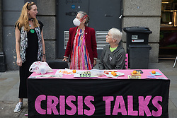 Environmental activists from Extinction Rebellion stand behind a Crisis Talks stall in the Covent Garden area during the first day of Impossible Rebellion protests on 23rd August 2021 in London, United Kingdom. Extinction Rebellion are calling on the UK government to cease all new fossil fuel investment with immediate effect. (photo by Mark Kerrison/In Pictures via Getty Images)