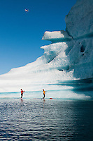 As a small plane flies overhead, two adults on stand up paddle boards (SUP) view an iceberg on Bear Lake in Kenai Fjords National Park, Alaska.