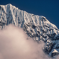Mount Kusum Khangri towers above clouds in the Dudh Kosi gorge, Khumbu Region,  Nepal.