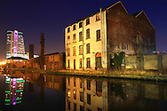 A long exposure / slow shutter speed photo taken in Leeds city center, United Kingdom, along the canal in the chilly January dusk as the still water mirrors the lights of the iconic Bridgewater Place, contrasting against the foreground derelict building, showing the changing times in Leeds.