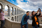Tourists taking selfie photographs with smartphone at famous spectacular Roman aqueduct, Segovia, Spain