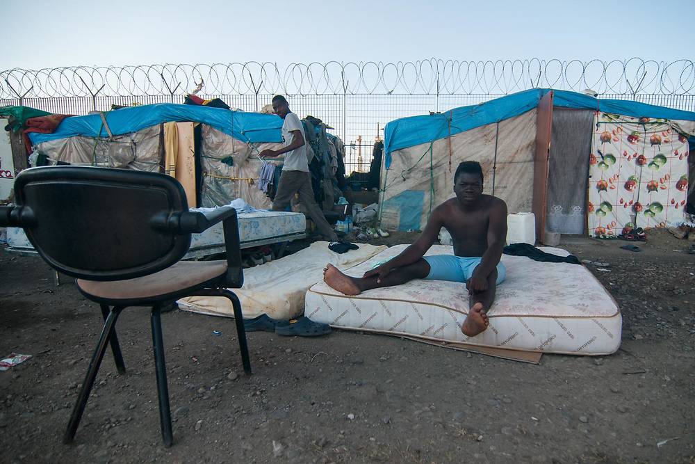 An illegal migrant from Mali wakes up in a camp near the railway station on August 03, 2017 in Crotone, Italy. The city of Crotone hosts one of the biggest european centre for migrants, but some of them live in clandestinity, even for two years, in an area near the city railway station, because they are afraid to be rejected and to be sent to their nations again. ©Simone Padovani