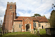 Tudor red brick porch set against more ancient building. St Peter's church, Charsfield Suffolk