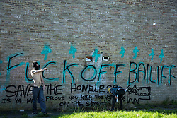 London, UK. 23 September, 2015.  Housing activists spray messages on a wall on the Sweets Way housing estate. A group of housing activists calling for better social housing provision in London occupied properties on the 142-home estate in Whetstone, in a few cases refurbishing properties intentionally destroyed by the legal owners following eviction of the original residents, in order to try to prevent the eviction of the last resident on the estate and the planned demolition and redevelopment of the entire estate by Barnet Council and Annington Property Ltd.