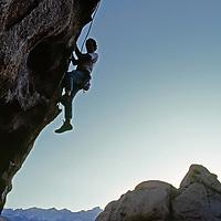 A climber ascends an overhang in the Buttermilk Rocks, near Bishop, California.