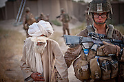 Corporal Michael Dutcher, 22, from Asheville, North Carolina, leads a detained Afghan elder into PB Fires. Dutcher was killed by an IED several weeks after this picture was taken.