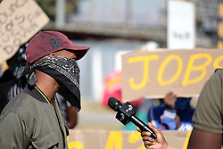 RUSTENBURG SOUTH AFRICA - MAY 18: A protester being interviewed by News Room Africa on May 18, 2020, in Rustenburg, South Africa. Seraleng residents gathered at Sibanye k5 mine shaft Communities in the area alleged complaints of food parcel corruption by a local ward councillor. Grievances also included concerns with unemployment, loss of business and access to a social labour plan. (Photo by Gallo Images/Dino Lloyd)