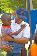 Black dad carrying son age 3 in his arms. Aquatennial Beach Bash Minneapolis Minnesota USA