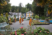 """Portmeirion, in North Wales, is a resort, where no one has ever lived. A self-taught Welsh architect named Sir Clough Williams-Ellis built it out of architectural salvage between the 1920s and 1970s, loosely based on his memories of trips to Portofino. Including a pagoda-shaped Chinoiserie gazebo, some Gothic obelisks, eucalyptus groves, a crenellated castle, a Mediterranean bell tower, a Jacobean town hall, and an Art Deco cylindrical watchtower. He kept improving Portmeirion until his death in 1978, age 94. It faces an estuary where at low tide one can walk across the sands and look out to sea. At high tide, the sea is lapping onto the shores. Every building in the village is either a shop, restaurant, hotel or self-catering accomodation. The village is booked out at high season, with numerous wedding receptions at the weekends. Very popular amongst the English and Welsh holidaymakers. Many who return to the same abode season after season. Hundreds of tourists visit every day, walking around the ornamental gardens, cobblestone paths, and shopping, eating ice-creams, or walking along the woodland and coastal paths, amongst a colourful assortment of hydrangea, rhododendrons, tree ferns and redwoods. The resort boasts two high class hotels, a la carte menus, a swimming pool, a lifesize concrete boat, topiary, pools and wishing wells. The creator describes the resort as """"a home for fallen buildings,"""" and its ragged skyline and playful narrow passageways which were meant to provide """"more fun for more people."""" It does just that.///Buddhist monks from Lichfield are tourists in Portmeirion. Ornamental central gardens of Portmeirion village. Flanked by Dome Gallery, Gothic tower, Renaissance collonades, with lwans, flowerbeds, topiary, pools and fountains."""