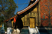 A monk works to repair the roof of Wat Xieng Thong, built in 1560 by King Setthathirath.The temple was under royal patronage during the Kingdom of Laos. Luang Prabang. In the late 1800s, French colonial powers and the Lao aristocracy of Vientiane developed a new architectural fusion in Luang Prabang, inspired by local temples and materials, and French and Indochine architecture. The French brought in skilled Vietnamese builders to build two-storey villas throughout the town.