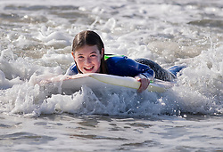 © Licensed to London News Pictures. 10/10/2018. West Wittering, UK. Teenage surfer Maddie from Surrey enjoys the waves at West Wittering as unseasonably high temperatures hit parts of the UK. Photo credit: Peter Macdiarmid/LNP