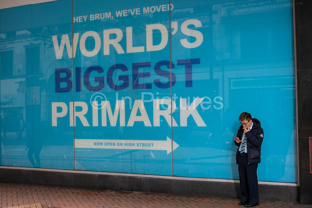 Man smoking while looking at his smart phone beside a large advert for Primark in Birmingham, United Kingdom. The Birmingham store is the biggest Primark in the World, and one of their flagship stores, selling clothes at the budget end of the market. The company sources cheaply, using simple designs and fabrics in the most popular sizes and buys stock in bulk.