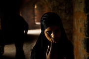 """10th December 2015, New Delhi, India. A Muslim woman in the ruins of Feroz Shah Kotla in New Delhi, India on the 10th December 2015<br /> <br /> PHOTOGRAPH BY AND COPYRIGHT OF SIMON DE TREY-WHITE a photographer in delhi<br /> + 91 98103 99809. Email: simon@simondetreywhite.com<br /> <br /> People have been coming to Firoz Shah Kotla to pray to and leave written notes and offerings for Djinns in the hopes of getting wishes granted since the late 1970's. Jinn, jann or djinn are supernatural creatures in Islamic mythology as well as pre-Islamic Arabian mythology. They are mentioned frequently in the Quran  and other Islamic texts and inhabit an unseen world called Djinnestan. In Islamic theology jinn are said to be creatures with free will, made from smokeless fire by Allah as humans were made of clay, among other things. According to the Quran, jinn have free will, and Iblīs abused this freedom in front of Allah by refusing to bow to Adam when Allah ordered angels and jinn to do so. For disobeying Allah, Iblīs was expelled from Paradise and called """"Shayṭān"""" (Satan).They are usually invisible to humans, but humans do appear clearly to jinn, as they can possess them. Like humans, jinn will also be judged on the Day of Judgment and will be sent to Paradise or Hell according to their deeds. Feroz Shah Tughlaq (r. 1351–88), the Sultan of Delhi, established the fortified city of Ferozabad in 1354, as the new capital of the Delhi Sultanate, and included in it the site of the present Feroz Shah Kotla. Kotla literally means fortress or citadel."""