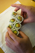 "Detail of a chef's hands, preparing Makizushi in 'So', a sushi restaurant in central London. Makizushi ""rolled sushi"" norimaki ""Nori roll"" or makimono ""variety of rolls"") is a cylindrical piece, formed with the help of a bamboo mat known as a makisu Makizushi is generally wrapped in nori (seaweed), but is occasionally wrapped in a thin omelette, soy paper, cucumber, or shiso (perilla) leaves. Makizushi is usually cut into six or eight pieces, which constitutes a single roll order. Below are some common types of makizushi, but many other kinds exist. So restaurant in Soho is contemporary Japanese dining infused with unique European flavours. Select dishes are prepared on our ""yogan-yaki"" customised grill and cooked over volcanic rocks imported from Mt. Fuji."
