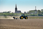 Nederland, Batenburg, 17-4-2020 Een boer, loonwerker, egaliseert de grond via een mechaniek achter de tractor. De grond is droog door het drie weken uitblijven van regen. Foto: Flip Franssen