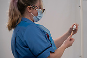 Vaccinator prepares a dose of the Oxford AstraZeneca vaccine at the new Millennium Point NHS Covid-19 Vaccination Centre on 11th January 2021 in Birmingham, United Kingdom. This coronavirus vaccination centre which is one of the first in the UK with the aim to vaccinate 15 million people by mid-February will administer 600 vaccines on its opening day, rising to 1200 on the following days and approximately 2500 per day as of the second week. Customers all receive a letter and can come to the vaccine centre from a 45 mile radius. Once in the vaccine lane they are asked health related questions and asked to give consent to being vaccinated after being advised of any possible side effects.