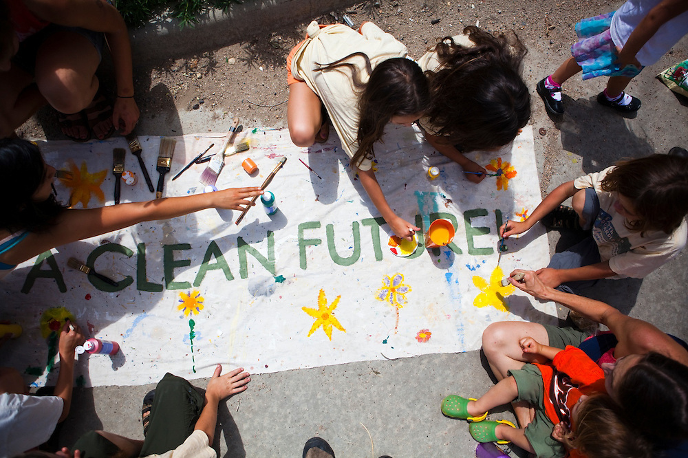 """Children paint a sign """"Plant a clean future"""" outside the coal-fired Valmont Power Plant in Boulder, Colorado in a protest of its continued operation. The all-ages group reached the site by riding bicycles from downtown."""