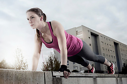 Young woman doing push-ups on ledge and listening to music, Bavaria, Germany