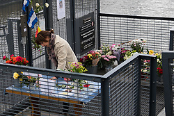 © Licensed to London News Pictures. 18/06/2016. LONDON, UK.  A woman looks at the floral tributes and stones of love and peace as they sign a condolence book on a tribute table outside Hermitage Moorings on the River Thames in Wapping, where the MP lived on a houseboat. The Labour MP for Batley and Spen was about to hold her weekly constituency surgery in Birstall Library on16 June 2016 when she was shot and stabbed in the street and later died. Friends and neighbours from the local community continue to visit Hermitage Moorings this morning to pay tribute to Jo Cox.  Photo credit: Vickie Flores/LNP