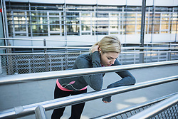 Exhausted jogger taking a break on city bridge